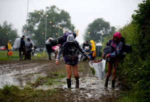Revellers carry their belongings as they arrive at Worthy Farm