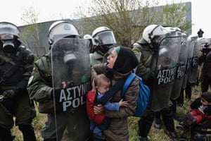 A woman holding a child confronts Greek riot police outside a refugee camp in Diavata, a suburb of Thessaloniki.