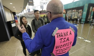 Timmy Bee, right, a volunteer at Seattle-Tacoma international airport in Seattle, gives sightseeing tips to travelers as he wears a sign that reads 'Thank a TSA worker Today!' on the back of his jacket on Friday.