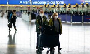 Passengers wearing face masks walk through arrivals at Heathrow