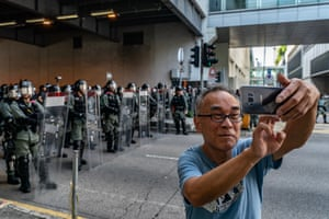 A pedestrian take a selfie as riot police stand guard during the anti-government rally in Tuen Mun.