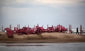 A man walks past tied up chairs at the Miramar beach as Hurricane Ingrid approaches the coast in Ciudad Madero, Mexico, in 2013.