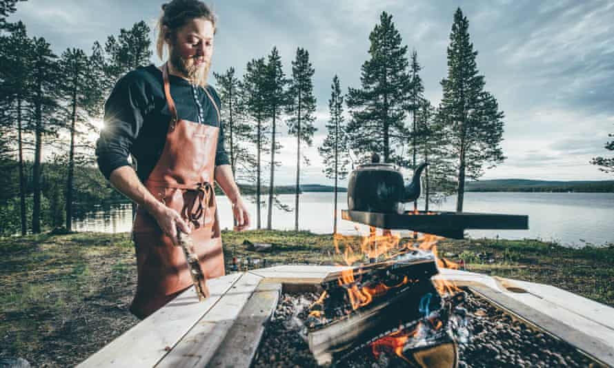 A young bearded man in an apron cooking outdoors over a fire, a lake and trees in the background