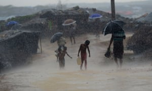 A Rohingya refugee child carries water during rain in a refugee camp in Bangladesh.
