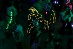 Revellers wear illuminated costumes