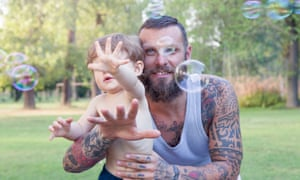 Child having fun with his dad and tries to take soap bubbles