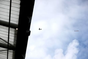 A plane flies over the ground with a banner reading #Glazersout.