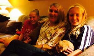 Kathleen Albertson at home with two of her four children, Grace (left) and Nora, holding the family hamster, Teddy.