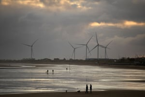 Windmills are seen as people exercise with their dogs on the beach