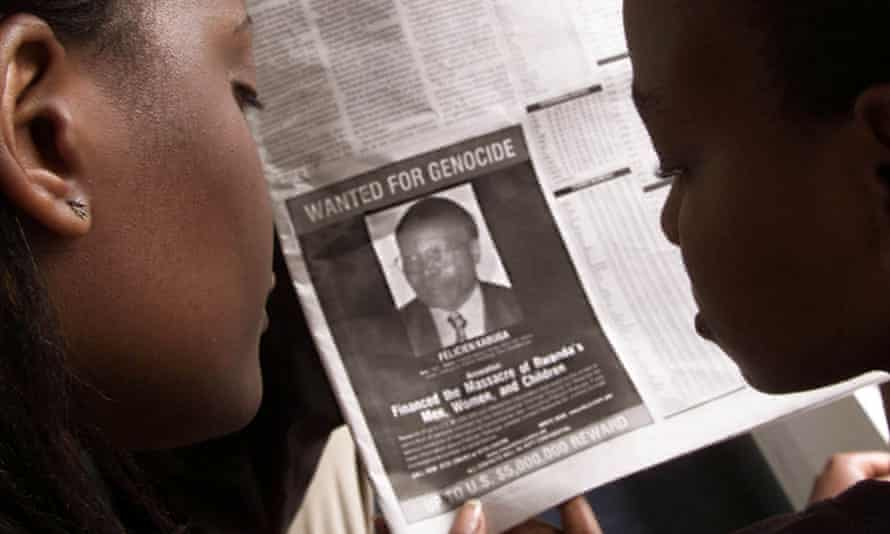 Women read a 'wanted' notice about Félicien Kabuga in a Kenyan newspaper.
