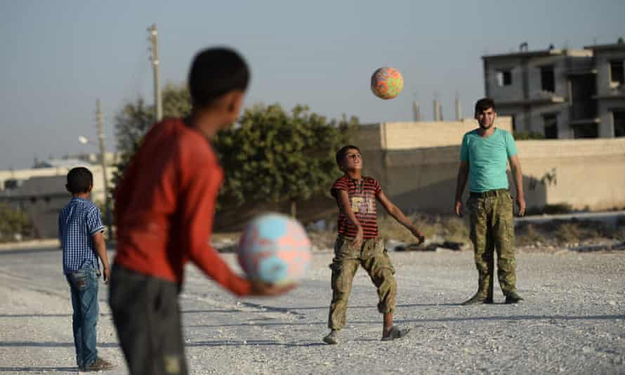 Syrian children play football with Free Syrian Army members.
