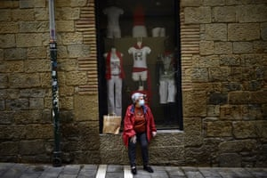 A woman rests in front a shop in Pamplona, northern Spain