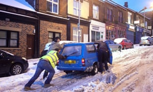 People in Sheffield struggle to push their car  through the snow