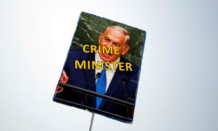 A protester holds a sign during a rally calling upon Benjamin Netanyahu to step down. The Israeli PM has been accused of bribery in two separate cases.