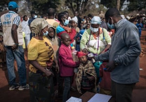 Ndu, Democratic Republic of Congo, An agent from the UNHCR performs a temperature check as part of the Covid-19 measures at the entrance of a refugee registration site
