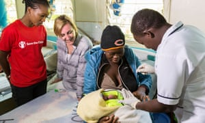 Tabitha Temko a health worker at the hospital applys CHX to Fridah Masake, 20yrs baby Fridah who is 3 days old while Pauline and Angela watch closely at the Ministry of Medical Services - Cheptais Sub-District Hospital, Kenya.