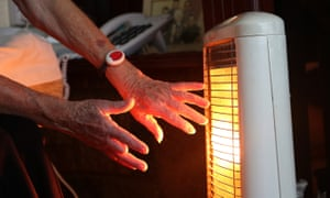 Elderly woman warms hands over electric fire