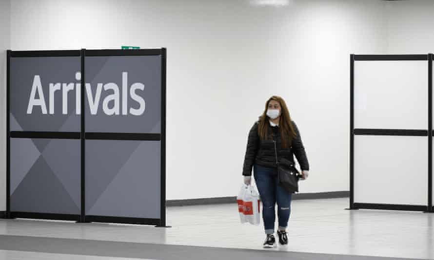 a lone woman emerges from arrivals hall