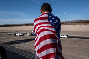 A Central American migrant wrapped in a US flag looks at the almost dry riverbed of the Tijuana River near the El Chaparral border crossing near US-Mexico border in Tijuana.
