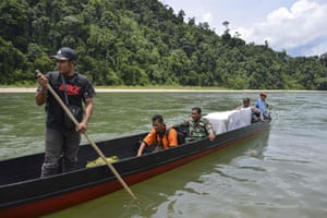 Indonesian election officials transport ballot boxes to a remote village by boat along a river in Manggamat, Southern Aceh province.