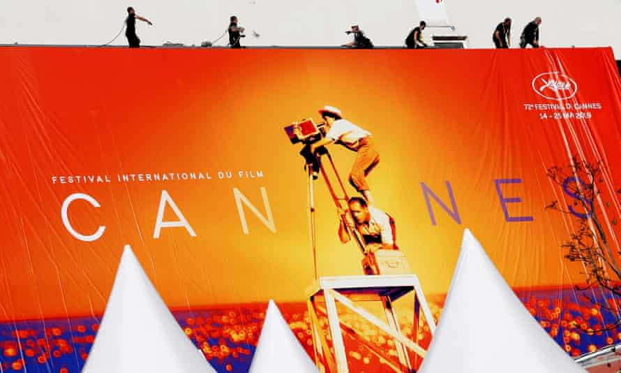Workers set up a giant canvas of the official Cannes poster on the facade of the festival palace.
