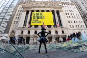 New York. People walk past a broken glass ceiling installation in front of the Fearless Girl Statue in front of the New York Stock Exchange.