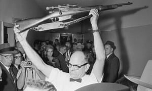 A Dallas policeman holds up the rifle used to kill President John F. Kennedy.