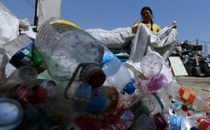 Beijing - A migrant worker dumps empty plastic bottles at a recycling centre in the capital's Changping suburb. It is one of the largest recycling centres in the city, with many migrant workers living there