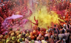 Nandgaon, India Men daubed in colours throw coloured powder at each other during Lathmar Holi celebrations