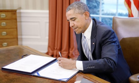 Obama signs the bill in the Oval Office.