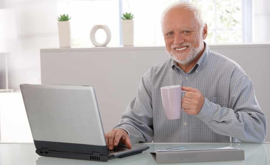 András Arató, aka Hide the Pain Harold, sitting at a desk, holding a mug