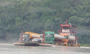 A ferry carrying two oil tankers across a river with lush green tress in the background