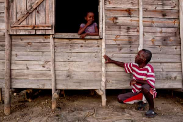 François, who has lived in Tanambao village, Madagascar, since 1998, shows his daughter a mark on his house that indicates the water level during last year's floods