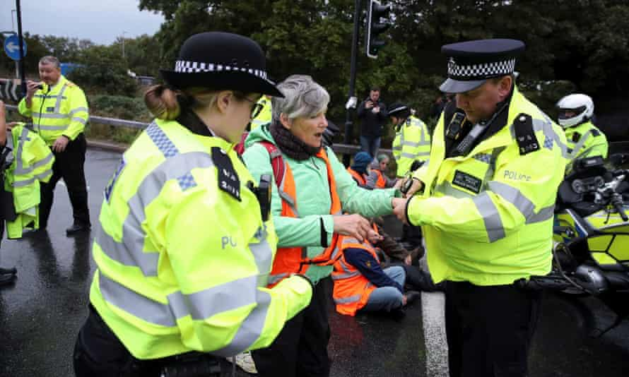 Police officers with an Insulate Britain activist at a motorway junction near Heathrow airport in London