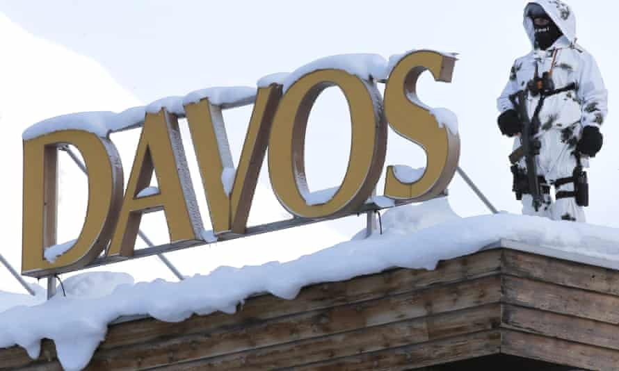 An armed officer is snow camouflage stands guard on a snow-covered roof by the big Davos sign