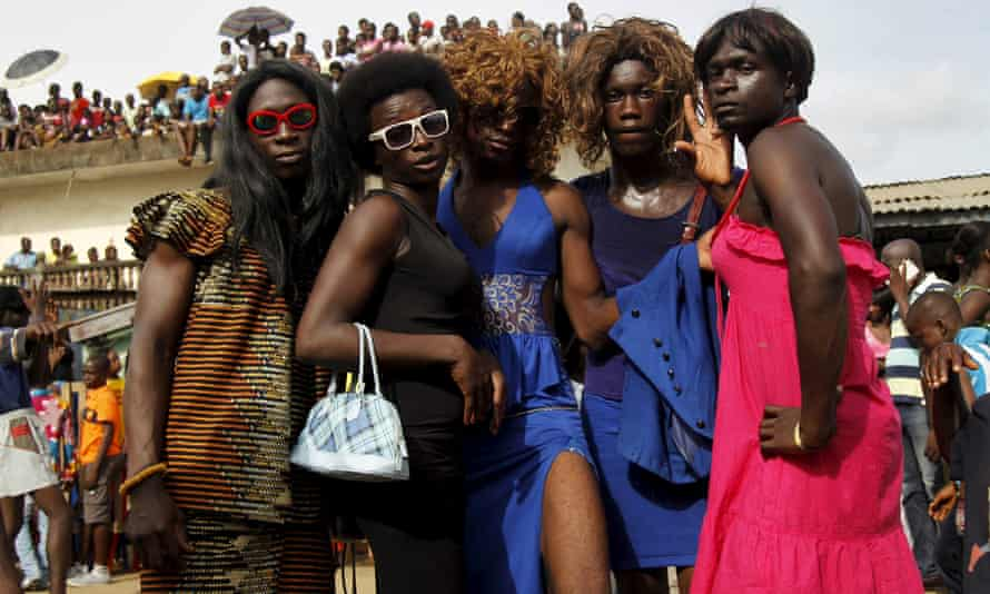 Men dressed as women take part in a parade during the a carnival in Abidjan,
