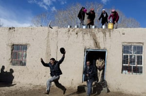<strong>Kashgar, China</strong><br>Tadjik women throw water over men from a roof top as they take part in a festival to celebrate the coming of spring