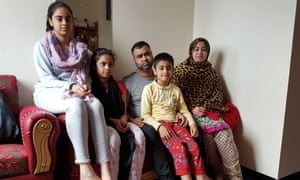 Nazmu Miah and family in their flat in Donald Hunter House, east London.