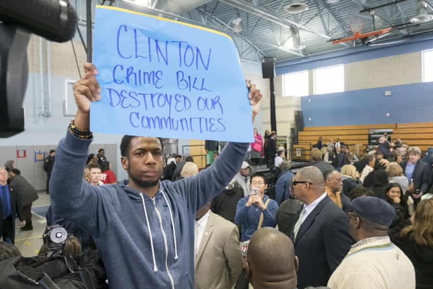 Protester Rosco Farmer is corralled in the back of the auditorium by civil affairs officers near the end of Bill Clinton's rally for Hillary Clinton.