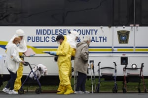 Residents from St Joseph's nursing home board a bus, after a number of residents tested positive for Covid-19 in Woodbridge, New Jersey, on 25 March.
