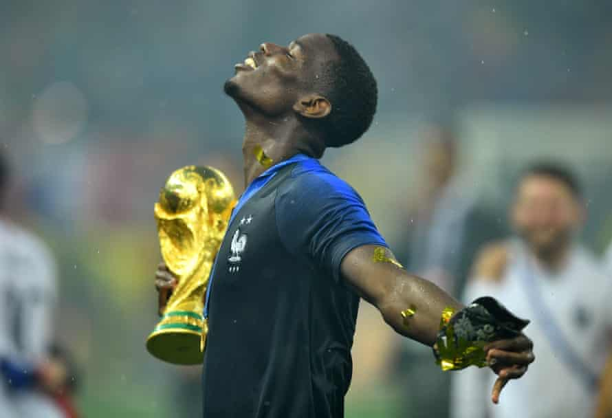 France's Paul Pogba holds the trophy as he celebrates.