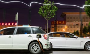Cars sit at a charging station in a residential compound in central Beijing