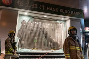 Firefighters in front of a vandalized branch of Hang Seng Bank on December 24, 2019.