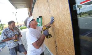 Mikes Jones (front) and Dan Steele boarded up a gas station Tuesday in preparation for Hurricane Michael in Panama City, Florida.