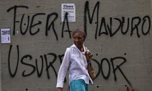 A woman walks past graffiti that says in Spanish: 'Get out Maduro. Usurper' in Caracas, Venezuela, on 24 January 2019