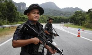 Malaysian police stand guard at the Malaysia-Thailand border in Wang Kelian.