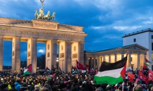 Protests in front of the Brandenberg Gate, Berlin, wave Palestinian flags