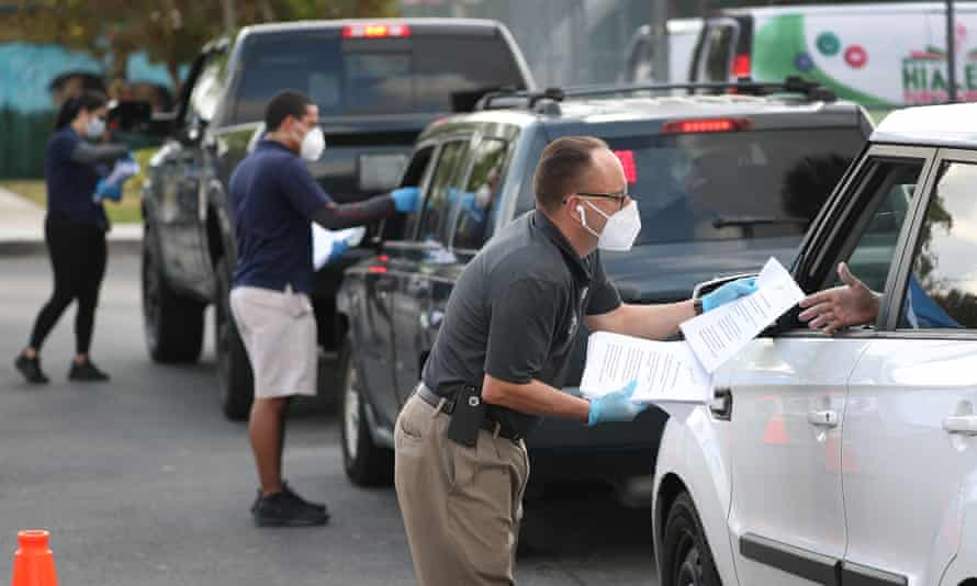 City employees hand out unemployment applications to people in their vehicles in front of the John F Kennedy library in Hialeah, Florida, on 8 April.