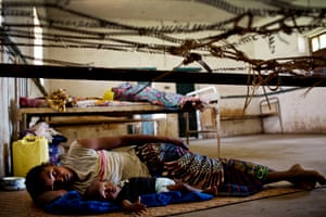 A woman and her baby, one of twins, lie in a neglected mission hospital in Kisangani in the Democratic Republic of the Congo, suffering from malaria