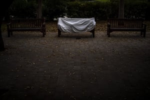 A homeless man covered by a sheet sleeps on a bench at a public park in Barcelona, Spain